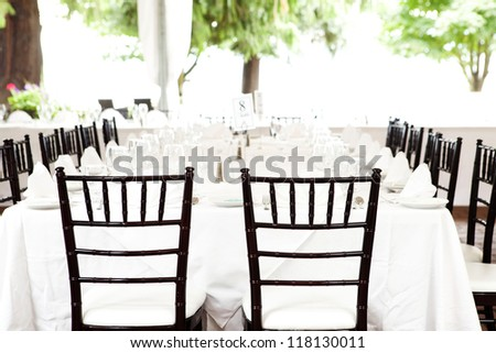 tables in open air outside - bride and groom chairs facing grouping - stock photo