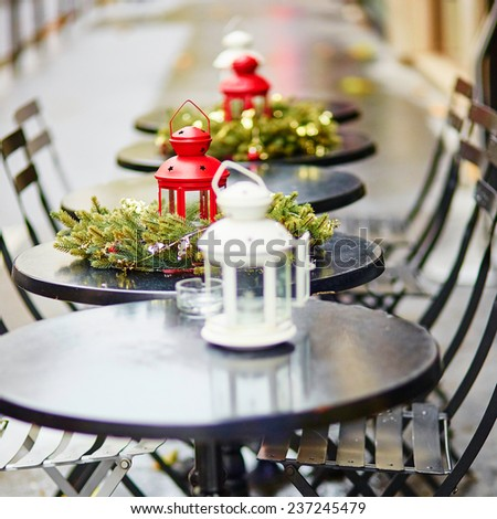 Tables of a Parisian outdoor cafe decorated for Christmas