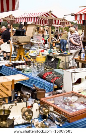 Tables on a flea market full of used things - stock photo