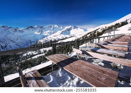 Tables on terrace covered by fresh snow near ski slopes on the top of Fellhorn Ski resort, Bavarian Alps, Oberstdorf, Germany - stock photo