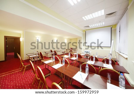 Tables with bottles and glasses, red chairs and projector in room for business trainings.  - stock photo
