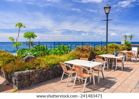 Tables with chairs of local restaurant on coast of Tenerife island in Puerto de la Cruz, Tenerife, Canary Islands, Spain - stock photo