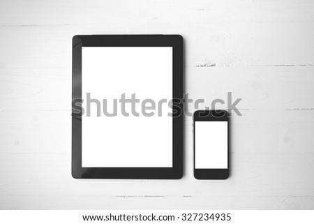 tablet and cellphone over white table black and white color style - stock photo