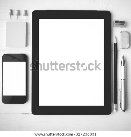 tablet and cellphone with office supplies over white table black and white color style