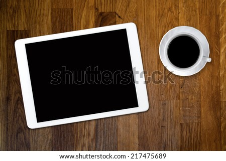 tablet and coffee on old wooden table - stock photo