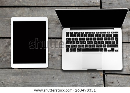 tablet and computer on old wooden table - stock photo