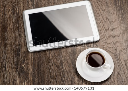 tablet and cup of coffee are on the table, still life