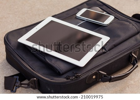 Tablet and mobile phone on a fashionable  bag. Copy space. Outdoor photo - stock photo