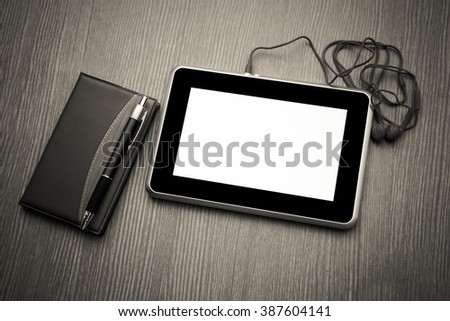 tablet and notepad on wooden floor