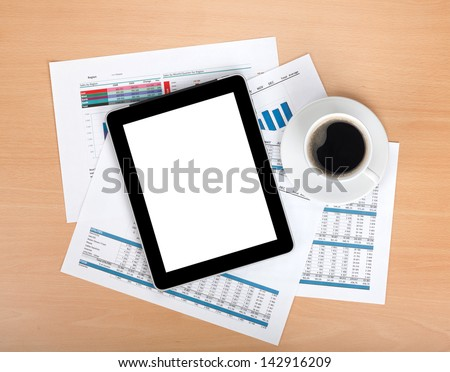 Tablet and notepad over papers with numbers and charts and coffee cup. View from above - stock photo