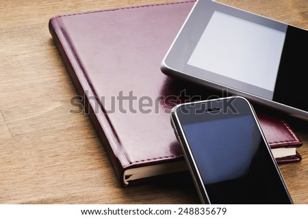 Tablet and phone with blank screen and notebook with leather cover on wooden table - stock photo