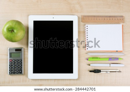 Tablet and school supplies on wooden table, top view - stock photo
