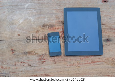 Tablet and Smart phone. Mobile phone and Tablet pc on wooden table - stock photo