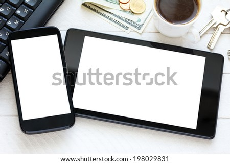 Tablet and smartphone with white blank screen on wooden table - stock photo