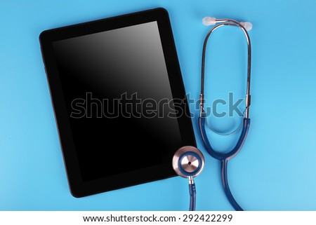 Tablet and stethoscope on blue background