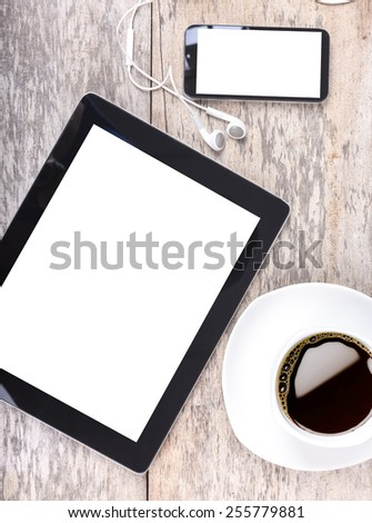 tablet and touch phone with isolated screen lie on a wooden with a cup of coffee - stock photo
