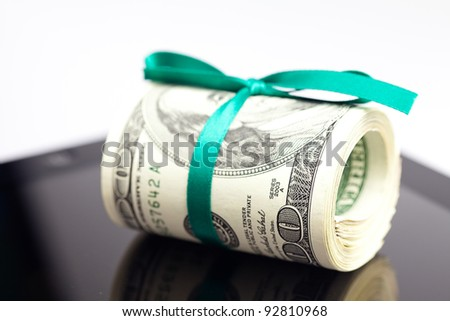 tablet and tube of dollars  isolated on white - stock photo