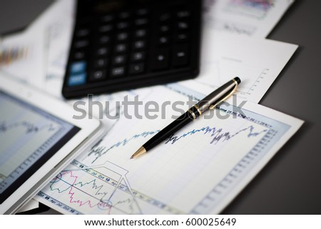 tablet,calculator,pen and financial charts in the workplace businessman