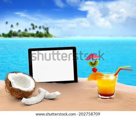 tablet, coconut and cocktail in the sand - stock photo