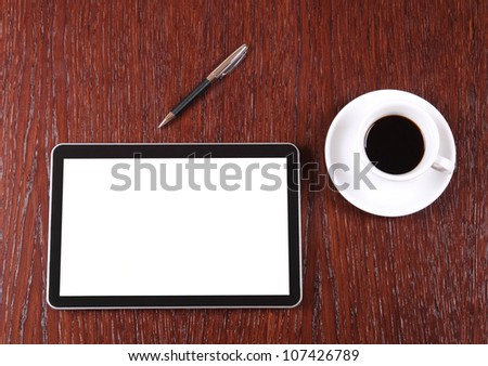 Tablet, coffee and pen on the desk