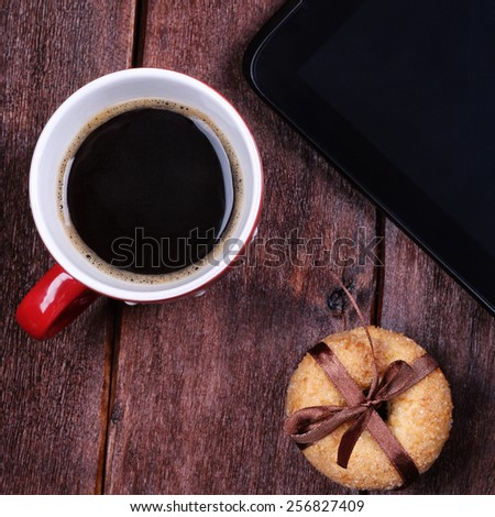 Tablet computer, a cup of black coffee and sugar cookies on the table. Kitchen table, a cup of black coffee and sweet biscuits. - stock photo