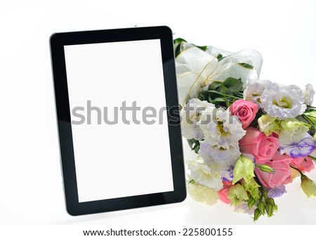Tablet computer and beautiful bouquet of flowers isolated on white - stock photo