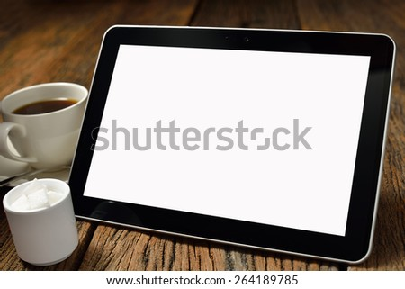 Tablet computer and coffee cup on old wooden background