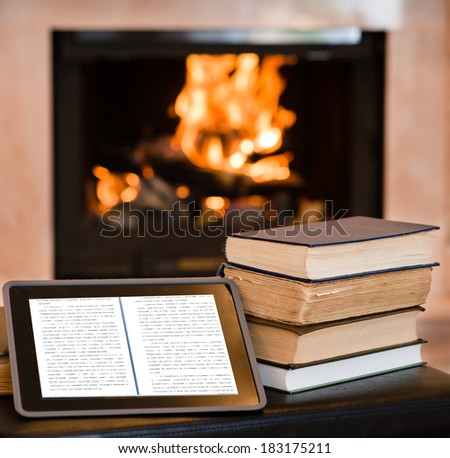 tablet computer and pile books on the background of the fireplace - stock photo