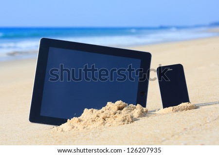 tablet computer and smartphone on the beach. - stock photo