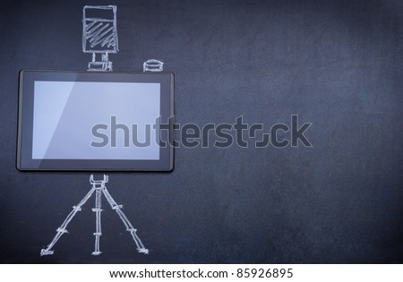 Tablet computer as photo camera on the blackboard with tripod and strobe drawn with chalk - stock photo