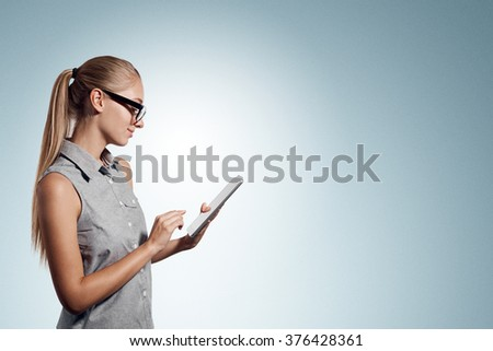 Tablet computer. Business woman using digital tablet computer PC happy isolated on white background. Beautiful woman in business shirt with finger on touch screen display. - stock photo