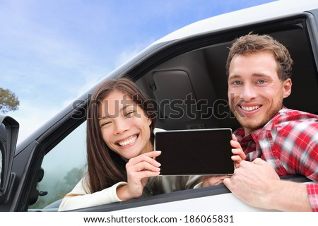 Tablet computer - couple driving in car showing screen with app or message. Young happy drivers on road trip. Asian woman, Caucasian man. - stock photo