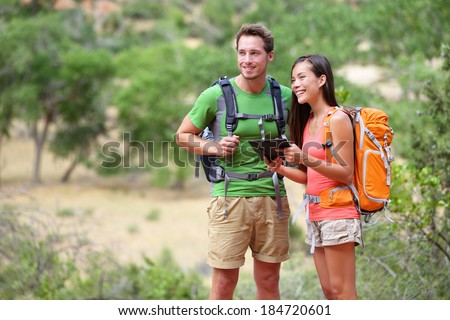 Tablet computer - couple hiking using internet and tablet computer pc guide book app on hike in Zion National Park. Interracial active hiker couple, Asian woman, caucasian man trekking in Utah, USA. - stock photo
