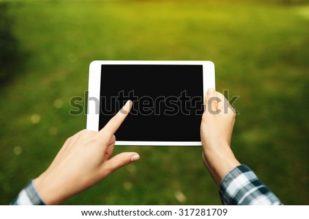 Tablet computer. Hipster woman using digital tablet computer PC. Girl touching tablet screen which is editable isolated on green background. - stock photo