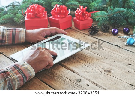 Tablet computer in men hands. Near the table with tablet computer red gift box, christmas toys and fluffy fir branches. Free space for text. top view. Copy space. Closeup - stock photo