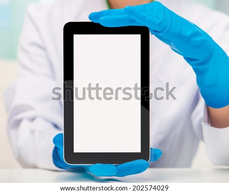 Tablet computer in the hands of the doctor with gloves - stock photo
