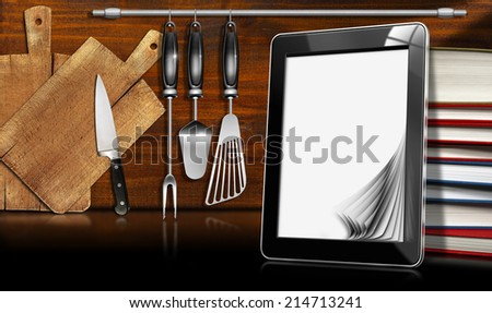 Tablet Computer in the Kitchen / Black tablet computer with blank pages and stack of books in a kitchen, on wooden wall with kitchen utensils. Template for recipes or food menu - stock photo