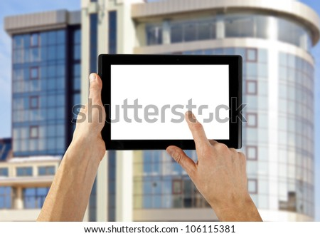 tablet computer isolated in a hand on the skyscraper backgrounds - stock photo