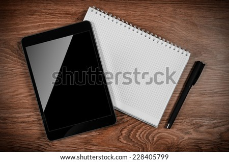 Tablet computer on the office table with notebook and pen. - stock photo