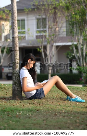 Tablet computer. Relaxed young  teenage in garden smiling content, happy and reading on tablet pc at home in garden. Lifestyle image of beautiful mixed Asian Caucasian girl relaxing smiling happy  - stock photo