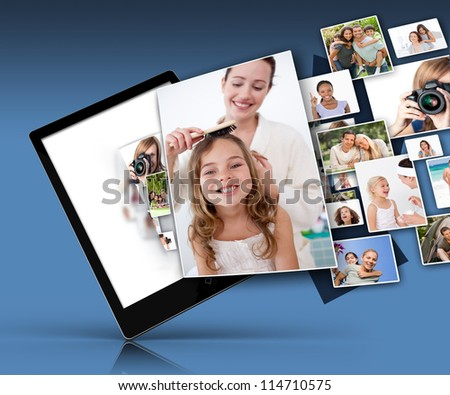 Tablet computer showing many family images on blue background - stock photo