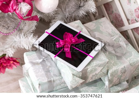 Tablet computer with a gift ribbon among other gifts