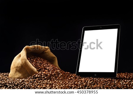 Tablet computer with blank white screen and coffee beans in burlap sack on black background - stock photo