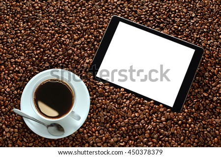 Tablet computer with blank white screen and cup of coffee on pile of coffee beans - stock photo