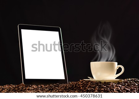 Tablet computer with blank white screen and cup of coffee with smoke on pile of coffee beans - stock photo