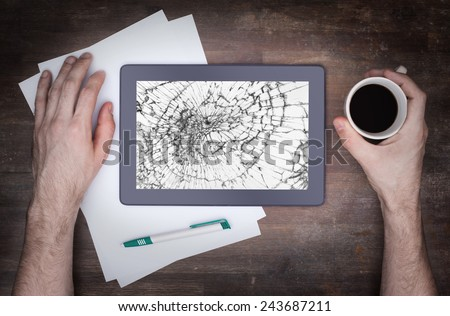 Tablet computer with broken glass, screen destroyed - stock photo