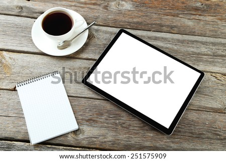 Tablet computer with notebook and cup of coffee on grey wooden background - stock photo