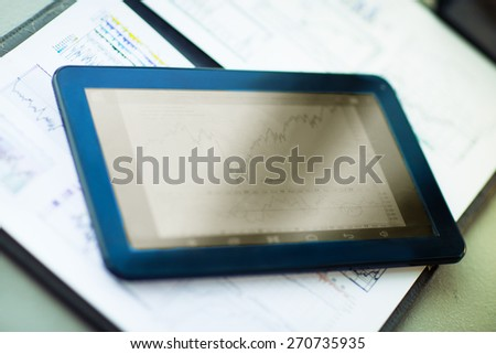 Tablet computer with the increasing time and financial documents - stock photo