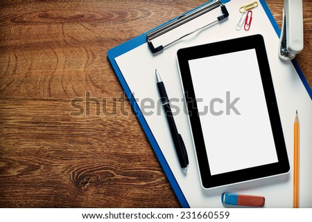 Tablet Device and Assorted Office Supplies on Clipboard with White Blank Paper on Wooden Desk. Emphasizing Copy Space at the Left Side.