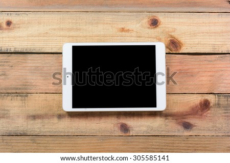 Tablet device, pen and note book on wooden workspace table - stock photo